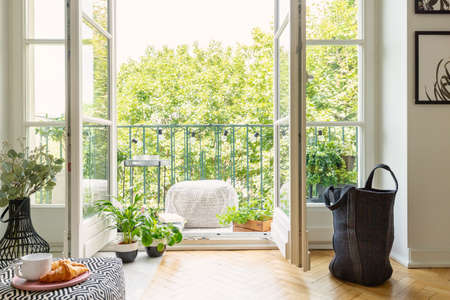 Foto de Open glass door from a living room interior into a city garden on a sunny balcony with green plants and comfy furniture - Imagen libre de derechos