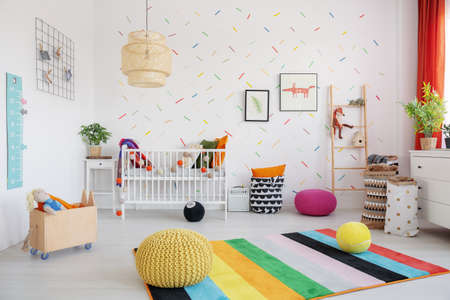 Foto für Poufs on colorful rug in scandi baby's bedroom interior with lamp, cradle and posters. Real photo - Lizenzfreies Bild