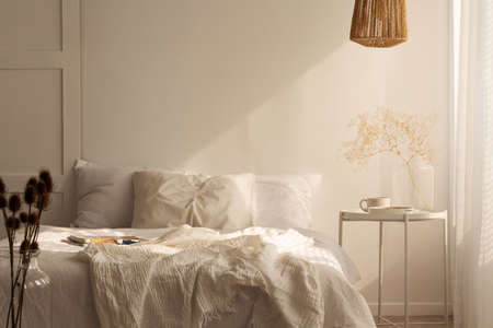 Photo pour Plant on table next to bed with pillows and sheets in white simple bedroom interior. Real photo - image libre de droit
