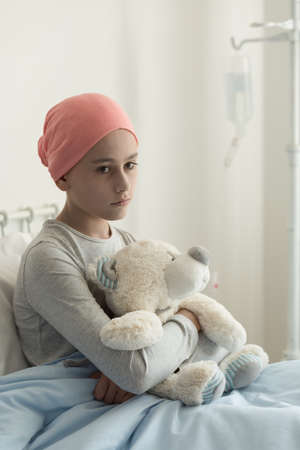 Photo for Sad lonely sick girl with cancer hugging plush toy in the hospital - Royalty Free Image