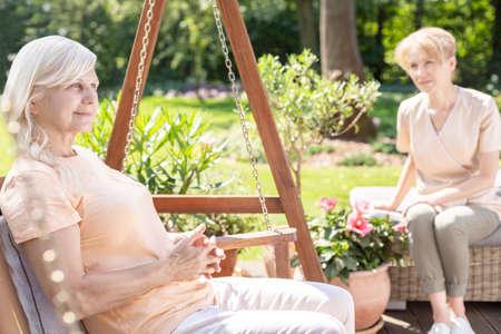 Foto de Smiling senior woman on hanging chair in the garden with caregiver - Imagen libre de derechos
