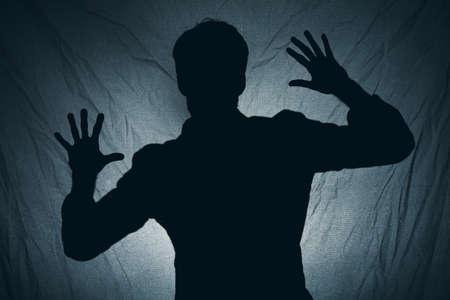 Foto de Shadow of a man behind dark fabric - Imagen libre de derechos