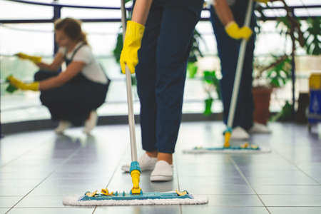 Photo pour Close-up on professional cleaner with yellow gloves and mop wiping the floor - image libre de droit