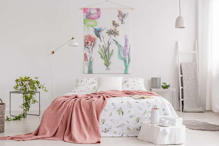 Photo pour Peach blanket and white with green pattern linen on bed in a natural bright bedroom interior. Tapestry with colorful flowers and birds on the back wall. Real photo. - image libre de droit