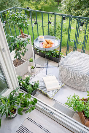 Photo pour Beautiful space for meal and relaxation on a green balcony with a comfy ottoman, string lights and a tray with sweet pastries and coffee - image libre de droit