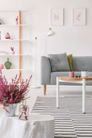 Foto de Heater in pot on the small wooden table in elegant scandinavian living room with grey couch and white lamp, real photo - Imagen libre de derechos