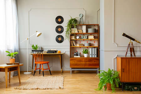 Photo pour Vinyl records decorations on a gray wall with molding and wooden furniture in a retro home office interior for a writer. Real photo. - image libre de droit