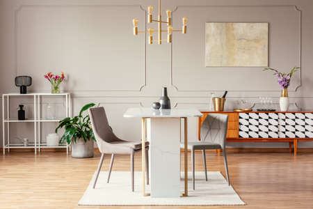 Foto de Industrial style, golden pendant light above an exceptional marble table in a trendy dining room interior with eclectic decor - Imagen libre de derechos