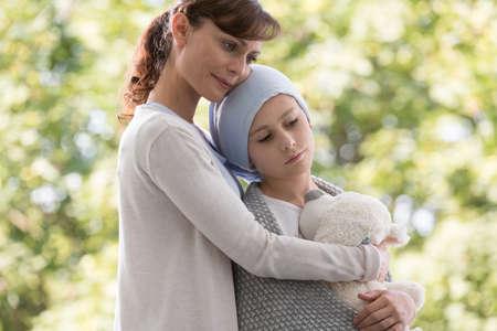 Foto de Mother hugging sad daughter with cancer - Imagen libre de derechos