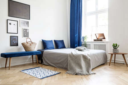 Photo for Bedroom design in modern apartment. Bed with dark blue pillows and grey duvet and blanket next to window. Real photo concept - Royalty Free Image