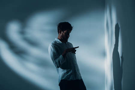 Foto de Man with schizophrenia standing alone in a room pointing at his shadow on the wall, real photo with copy space - Imagen libre de derechos