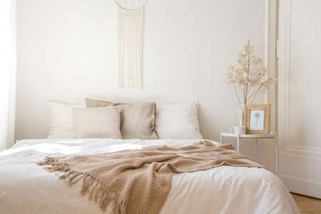 Foto de King size bed with white bedding, beige pillows and blanket next to bedside table with flower, coffee bug and print in frame, real photo - Imagen libre de derechos