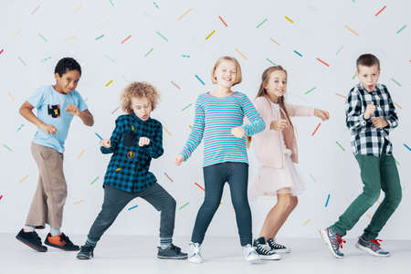 Photo for Smiling girls and boys dancing together in the school against colorful wallpaper - Royalty Free Image
