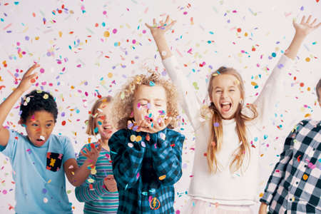 Photo pour Happy multicultural group of kids having fun during birthday party with confetti - image libre de droit