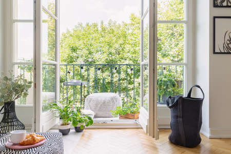 Foto de Green plants in pots in open door to balcony with small stylish table and pouf, real photo - Imagen libre de derechos