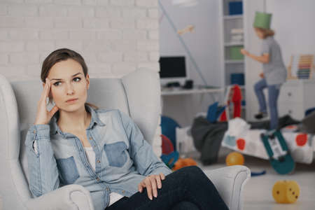 Foto de Worried mother relaxing on armchair while son with adhd making a mess - Imagen libre de derechos