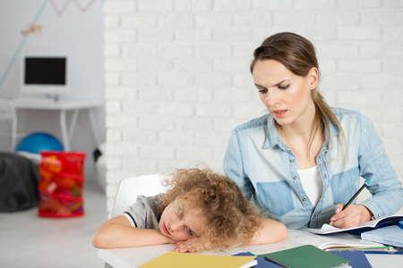 Foto de Nervous mother doing homework with bored kid with Asperger syndrome - Imagen libre de derechos