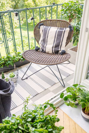 Foto de Top view of stylish rattan chair with patterned pillow on the balcony of modern flat, real photo - Imagen libre de derechos
