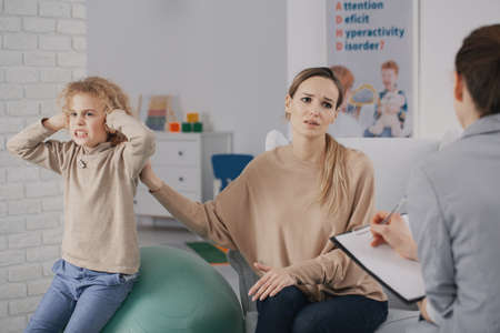 Foto de Sad woman and rebellious child with adhd during therapy with psychotherapist - Imagen libre de derechos