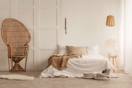 Foto de Stylish peacock chair in elegant bedroom created with natural materials, real photo with copy space on the empty wall - Imagen libre de derechos