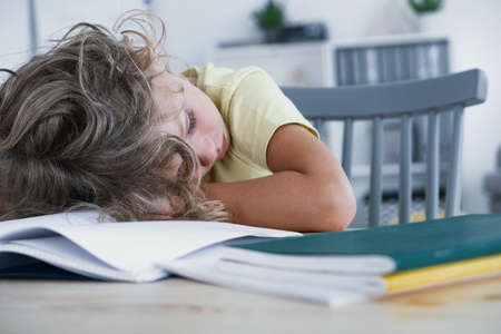 Foto de Close-up of a tired kid sleeping with his head rested on a table with a book. - Imagen libre de derechos