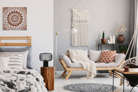 Photo pour Small open space flat interior with beige sofa with cushion, macrame on the wall, rack with candles and plants and bed with pillows - image libre de droit