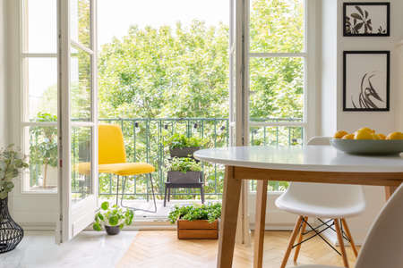 Photo pour Yellow chair on the balcony of elegant kitchen interior with white wooden chair and posters on the wall, real photo - image libre de droit