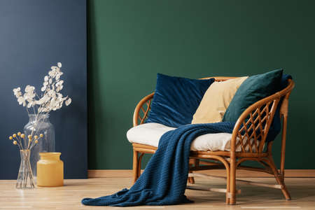 Photo pour Glass vases with flowers next to comfortable rattan settee with blue, emerald and beige pillows and blanket, real photo with copy space on empty green wall - image libre de droit