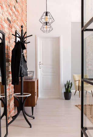 Foto de Vertical view of elegant entrance hall with white door and wooden furniture in stylish apartment with brick wall, real photo - Imagen libre de derechos