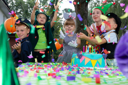Photo for Smiling kids wearing in carnival costumes during colorful birthday party with cake - Royalty Free Image