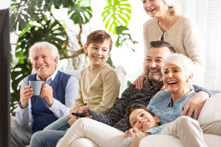 Photo pour Happy family watching television. Kids sitting next to parents and smiling grandfather - image libre de droit