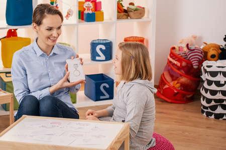 Foto de Smiling therapist showing picture of ring during meeting with autistic girl - Imagen libre de derechos