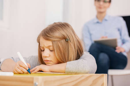 Foto de Concentrated girl holding pen while writing exercises during classes - Imagen libre de derechos