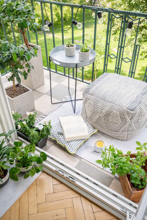 Photo for Top view of balcony with lights, fresh plants, mug with tea, open book and material pouf in real photo - Royalty Free Image