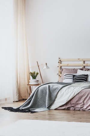 Foto de Lamp and plant on table next to wooden bed with grey and pink sheets in bedroom interior. Real photo - Imagen libre de derechos