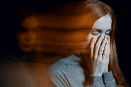 Photo for Blurred picture of young beautiful redhead girl with depression covering her mouth - Royalty Free Image