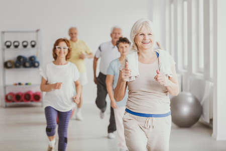 Foto de Happy senior woman with towel exercising during fitness classes for elderly people - Imagen libre de derechos