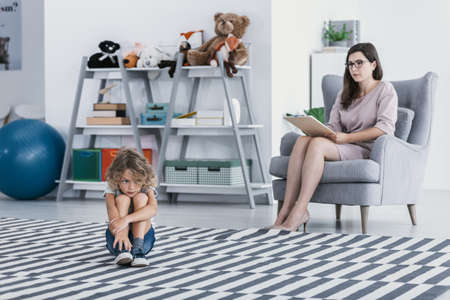 Foto de Sad and lonely kid and psychotherapist during treatment in the office - Imagen libre de derechos