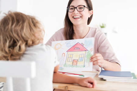 Foto de Smiling psychologist with home picture and child in a family support centre - Imagen libre de derechos