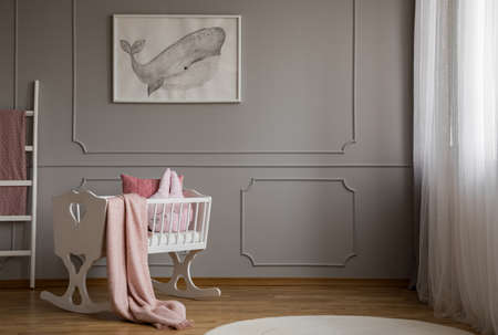 Foto de Whale on poster on the empty grey wall of cute baby bedroom interior with white cradle with pillow and paste pink blanket - Imagen libre de derechos