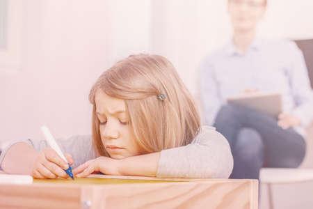 Foto de Concentrated girl holding pen while doing exercises during extra-curricular classes - Imagen libre de derechos