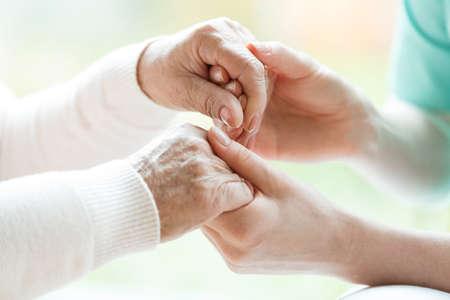 Foto de Closeup of the hands of a young woman holding hands of an elderly lady - Imagen libre de derechos