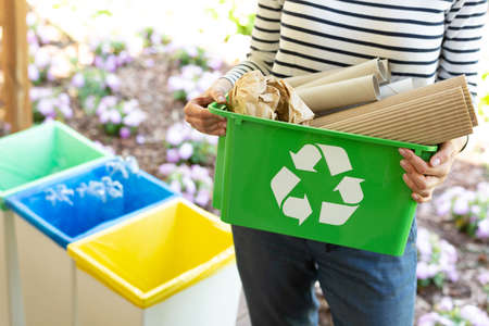 Foto de Close-up of a green basket with a recycling symbol with papers held by a woman - Imagen libre de derechos