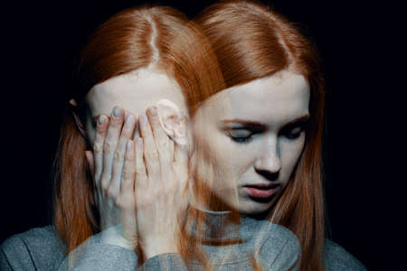 Foto de Porter of beautiful redhead girl with psychotic disorders covering her face, hiding from her hallucinations, black background behind her - Imagen libre de derechos