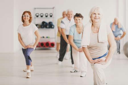 Foto de Smiling senior woman with towel exercising during yoga classes for elderly people - Imagen libre de derechos