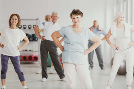 Photo for Happy senior woman holding hips during gymnastic classes for elderly people - Royalty Free Image