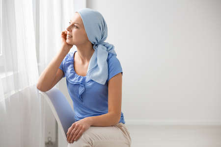 Photo pour Smiling teenage girl suffering from brain tumor, wearing blue headscarf and sitting on chair in hospital waiting hall, looking through the window, copy space on the empty wall - image libre de droit