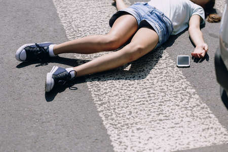 Foto de Unconscious girl lying on a street next to her mobile phone - Imagen libre de derechos