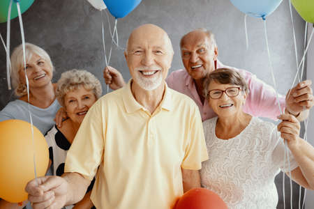 Photo pour Smiling elderly people with balloons having fun during friend's birthday - image libre de droit