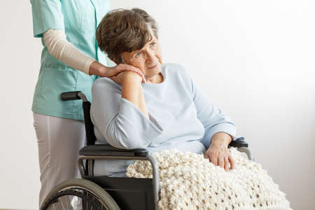 Foto de Nurse supporting sad disabled elderly woman in the wheelchair - Imagen libre de derechos